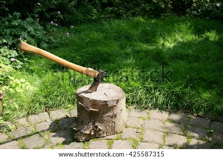 Chopping block with woodcleaver axe in a garden. - stock photo