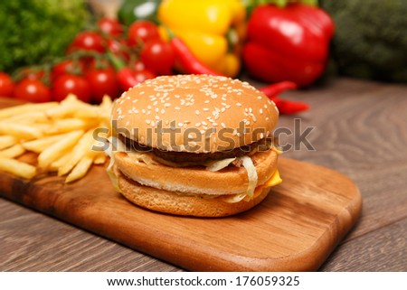 Chopping board with fried and burger - stock photo