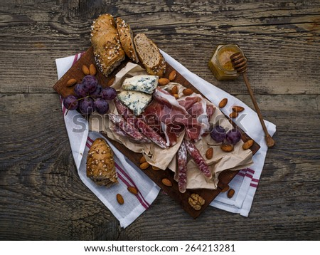Chopping board with meat selection and cheese, nuts and plums on dark wooden background