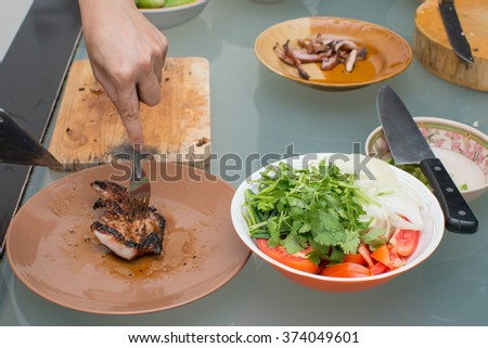 Chopping cooked roast beef and pork preparing to eat with another ingredient - stock photo