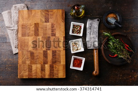 Chopping cutting kitchen board, seasoning, herbs and Butcher meat cleaver on dark wooden background - stock photo