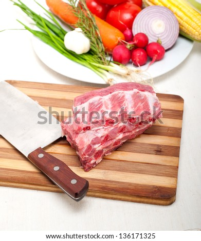 chopping fresh pork ribs with vegetables and herbs ready to cook - stock photo