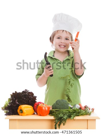 Chopping Vegetables.  Adorable preschooler wearing a chef's hat and cutting up vegetables.  Isolated on white.