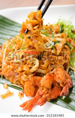 chopstick lifting up fried noodle