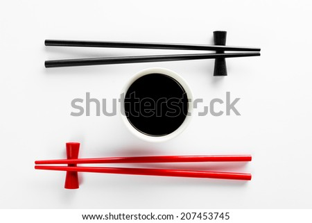 Chopsticks and bowl with soy sauce on bamboo mat - stock photo