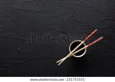Chopsticks and bowl with soy sauce on black rock - stock photo