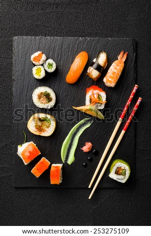 Chopsticks and bowl with soy sauce on wooden table - stock photo