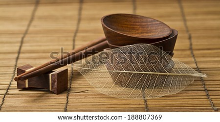 chopsticks and bowls on a bamboo mat  - stock photo