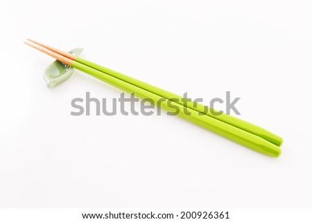 Chopsticks and chopstick-rest on a white background - stock photo