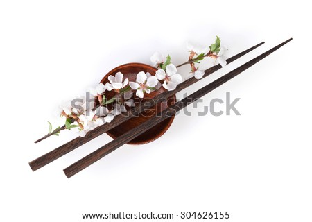 Chopsticks and sakura branch over soy sauce bowl. Isolated on white background - stock photo