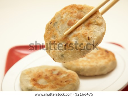 Chopsticks holding chinese traditional meat pie.