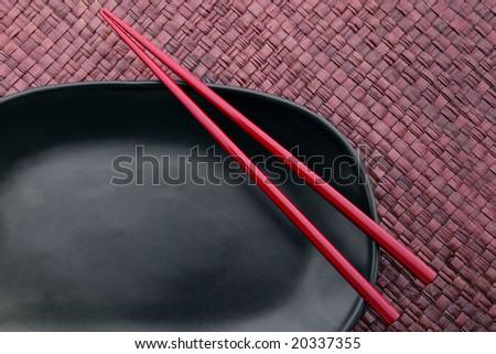 Chopsticks on a black plate - stock photo