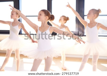 Choreographed dance by a group of graceful pretty young ballerinas practicing during class at a classical ballet school - stock photo