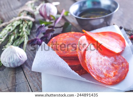 chorizo and aroma spice on paper and on a table - stock photo