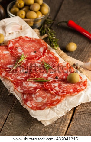 Chorizo sausage and salami, thin cut. spanish salami on the wood background with spices, paprika, pepper. Spicy food. Chili. - stock photo