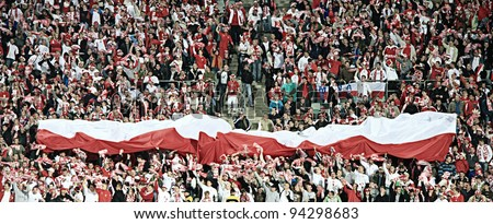 CHORZOW - SEPTEMBER 5: Polish fans in Slaski stadium cheer during the 2010 FIFA World Cup qualification match between Poland and Northern Ireland on September 5, 2009 in Chorzow, Poland. - stock photo