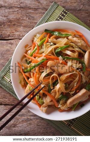 Chow Mein: fried noodles with chicken and vegetables close-up. vertical top view  - stock photo