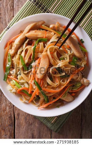 Chow mein with chicken and vegetables close-up. top view of the vertical  - stock photo