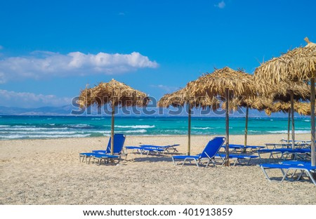 Chrisi (Chrysi) island beach background with straw sunshades, Crete, Greece. One of the most beautiful uninhabited island of Greece. - stock photo