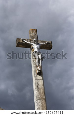christ on cross with dark clouds as background - stock photo