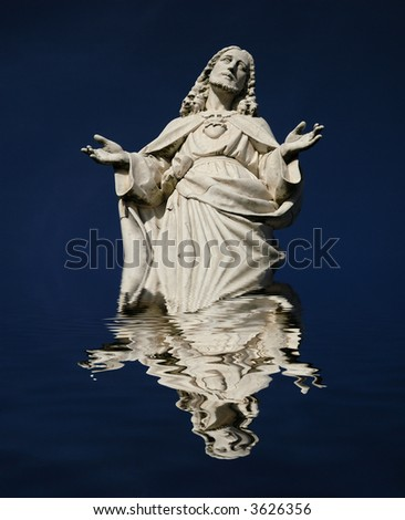 christ statue detail with reflection on the water