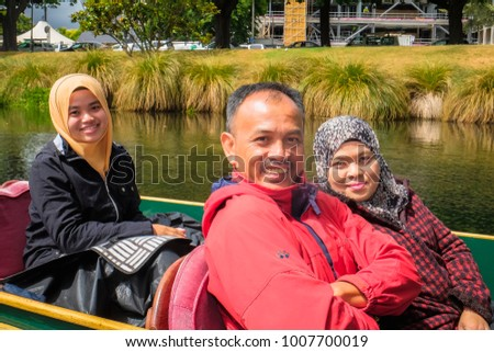 Christchurch, New Zealand â?? December 14th ,2017 :  Young girl wearing hijab  and her parents  punt on the Avon River, passing through Hagley Park, in Christchurch, New Zealand.