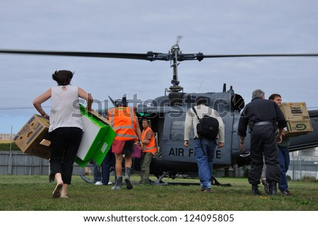 CHRISTCHURCH, NEW ZEALAND: FEB 22: Volunteer workers scramble for supplies from Air Force Iroquois helicopter after the 6.4 earthquake in Christchurch, South Island, New Zealand, 22-2-2011 - stock photo