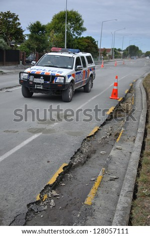 CHRISTCHURCH, NEW ZEALAND, FEBRUARY 26, 2011 - A police car drives past road damage caused in the 6.3 magnitude earthquake in Christchurch, South Island, New Zealand, 22-2-2011 - stock photo