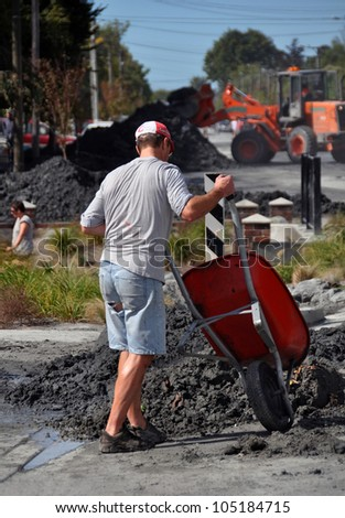 CHRISTCHURCH, NEW ZEALAND - FEBRUARY 24: Unknown man wheelbarrows earthquake liquefaction from his house on February 24, 2011 in Christchurch. - stock photo