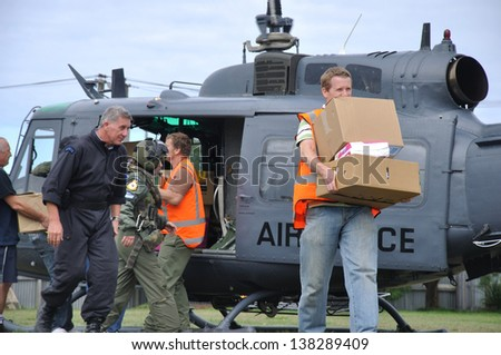CHRISTCHURCH, NEW ZEALAND, FEBRUARY 22, 2011: Volunteer relief workers scramble for food supplies from an Air Force Iroquois helicopter after the big earthquake in Christchurch, New Zealand, 22-2-2011