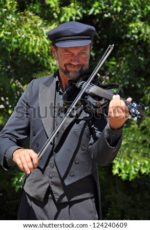 CHRISTCHURCH, NEW ZEALAND - JANUARY 24,  2011: The Violinist entertains the lunchtime crowds at the 18th World Buskers Festival on January 24, 2011 in Christchurch. - stock photo
