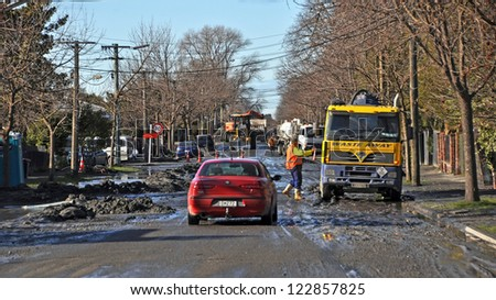 CHRISTCHURCH, NEW ZEALAND - JUNE 15, 2011:  Construction workers remove tons of liquefaction covering Retreat Road, Avonside after recent earthquakes on June 15, 2011 in Christchurch. - stock photo
