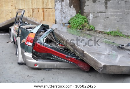 CHRISTCHURCH, NEW ZEALAND - MARCH 20: A car is crushed by a collapsed concrete wall on March 20, 2011 in Christchurch following a 6.2 magnitude earthquake. - stock photo
