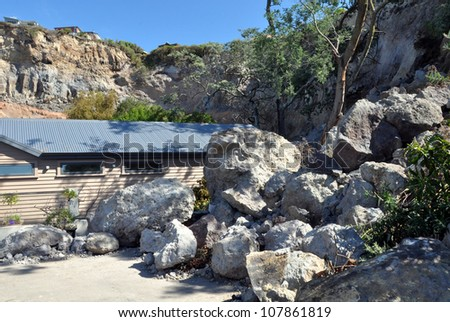 CHRISTCHURCH, NEW ZEALAND - MARCH 25: House escapes hundreds of tons of earthquake rocks that fell from the cliffs at Redcliffs on March 25, 2011 in Christchurch. Houses on the ridge uninhabitable. - stock photo