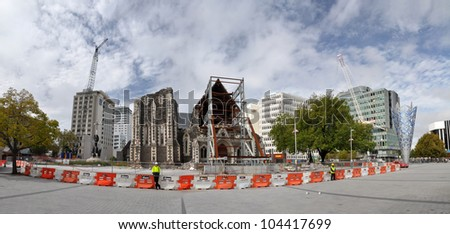 CHRISTCHURCH, NEW ZEALAND - MARCH 10: Panoramic view of the ruins of the Anglican Cathedral on March 10, 2012 in Christchurch, New Zealand. In the background cranes dismantle the remaining office blocks. - stock photo