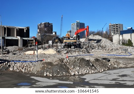 CHRISTCHURCH, NEW ZEALAND - MAY 27: An excavator sits atop a pile of rubble that was before recent earthquakes the iconic Park Royal Hotel in Victoria Street on May 27, 2012 in Christchurch. - stock photo