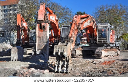 CHRISTCHURCH, NEW ZEALAND - MAY 21, 2011: Three machines of mass destruction  designed to tear down buildings, cut steel reinforcing and scoop up the debris on May 21, 2011 in Christchurch. - stock photo