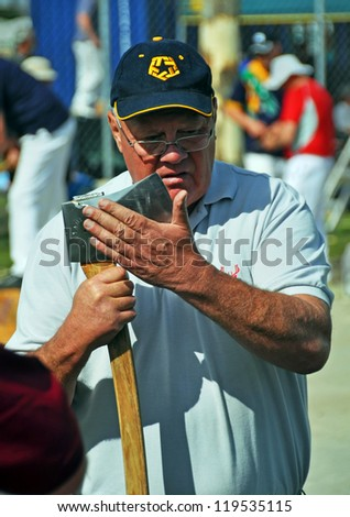 CHRISTCHURCH, NEW ZEALAND - NOVEMBER 16: Competitor sharpens his axe at the 2012 Canterbury A&P Show wood chopping competition on November 16, 2012 in Christchurch. - stock photo
