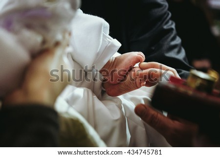 christening of little baby in church, close-up feet and priest hand - stock photo