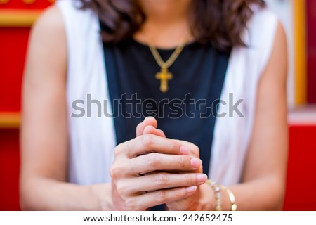 Christian believer praying to God with Cross rosary in her Neck.Focus on Hand - stock photo