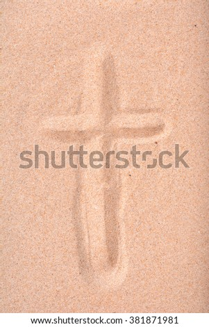 Christian cross drawn in beach sand.