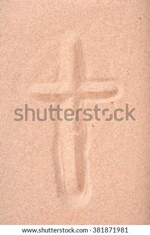 Christian cross drawn in beach sand. - stock photo
