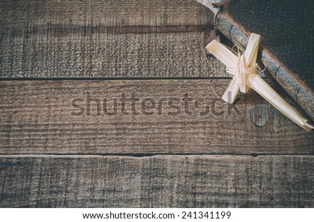 Christian Cross handmade of Dried Grass against Old Bible on rustic wood board background with empty room or space for copy, text, your words.  Horizontal vintage grunge
