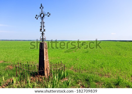 Christian Cross in a field of grass - stock photo