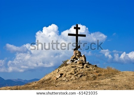 christian cross in a hill on a blue sky background - stock photo