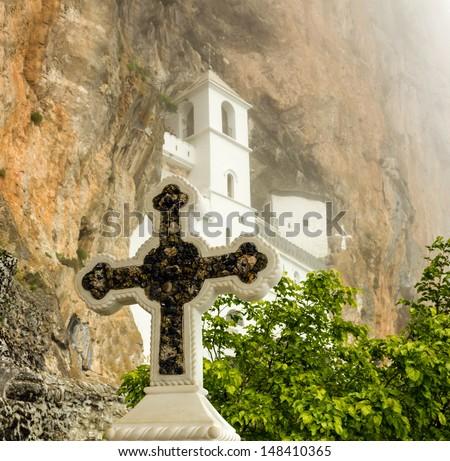 Christian cross in rocky Serbian Orthodox monastery Ostrog, Montenegro - stock photo
