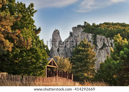 Christian cross on top of a cliff in the mountains. - stock photo