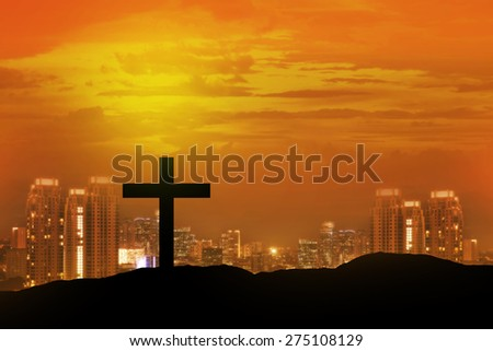 Christian cross with sunset sky and city on the background - stock photo