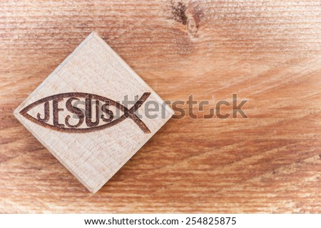 Christian fish symbol carved in wood hanging on old rustic wood background - stock photo