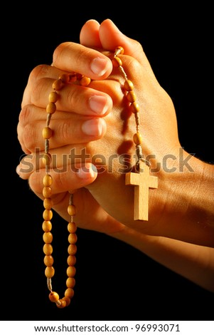 Christian human praying with rosary in hands - stock photo
